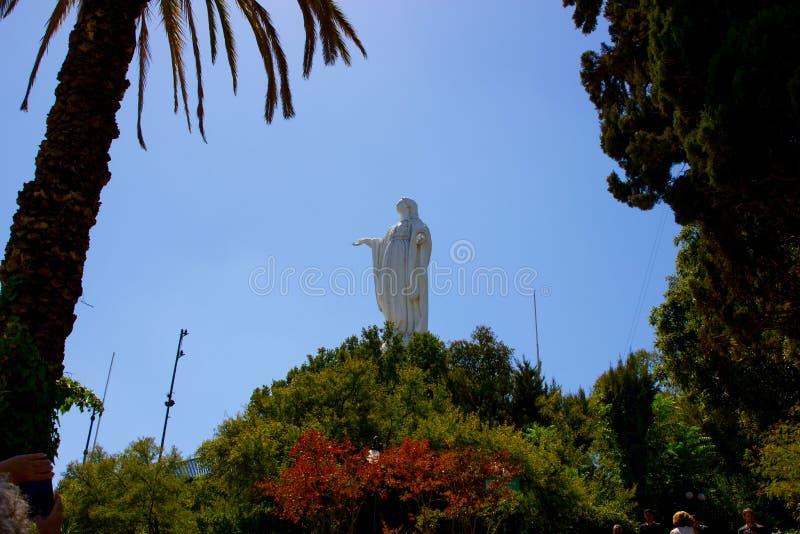 La statua di vergine Maria sta alta sopra i giardini su Cerro San Cristobal un bello giorno con i chiari cieli blu immagini stock