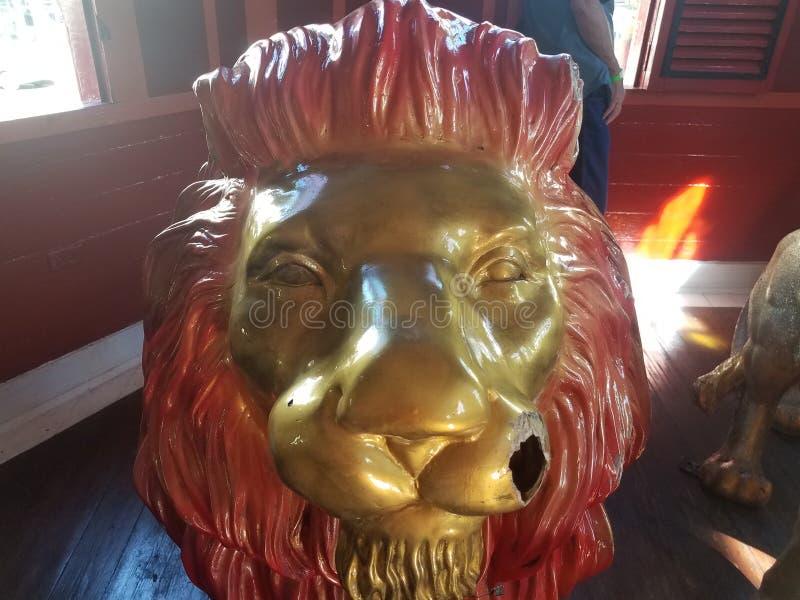 La statue animale de lion avec le visage a peint l'or et le trou dans le visage photo libre de droits