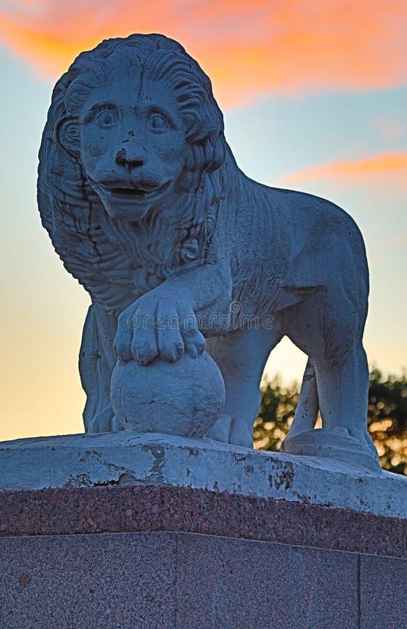 La statue d'un lion tenant sa patte sur la cuvette en parc sur le fond du coucher du soleil pendant la nuit blanche à Pétersbourg images libres de droits