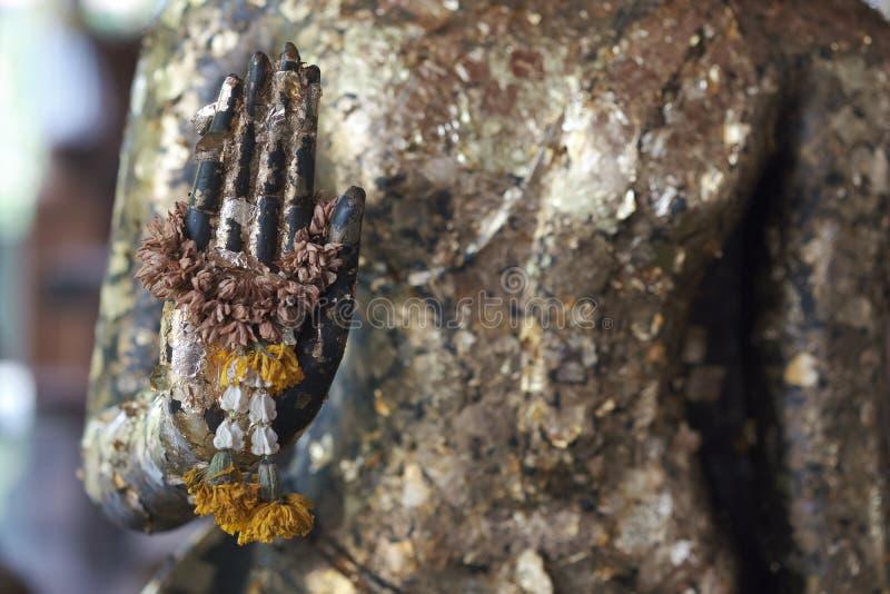La statue de Bouddha de feuille d'or d'attache en main et le vieux Jasmine Wreaths ou guirlandes, Buddism font le mérite à l'aide photo stock