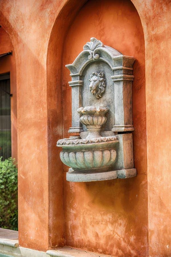 La statue de visage du ` s de lion a découpé sur le mur d'un bâtiment images libres de droits