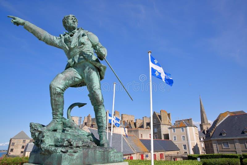 La statue du corsaire Robert Surcouf érigée en 1903 avec la ville murée de Saint Malo à l'arrière-plan photos stock