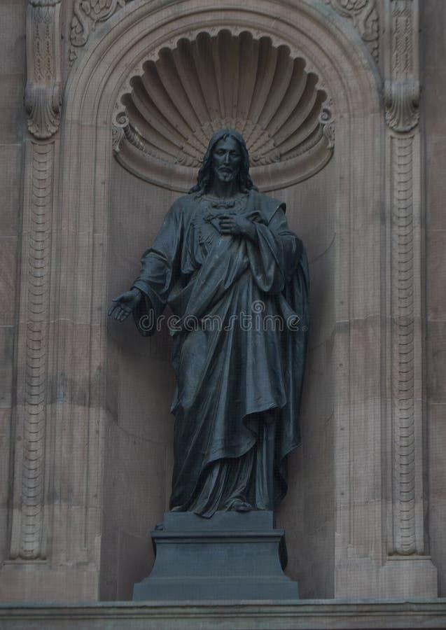 La statue sacrée de bronze de ` de coeur de ` de Jésus dans un créneau sur l'avant de la basilique de cathédrale des saints Peter photo libre de droits