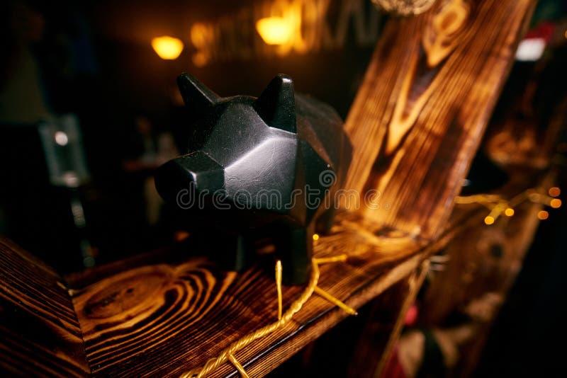 La statuetta nera del maiale sta su uno scaffale di legno giallo fotografia stock