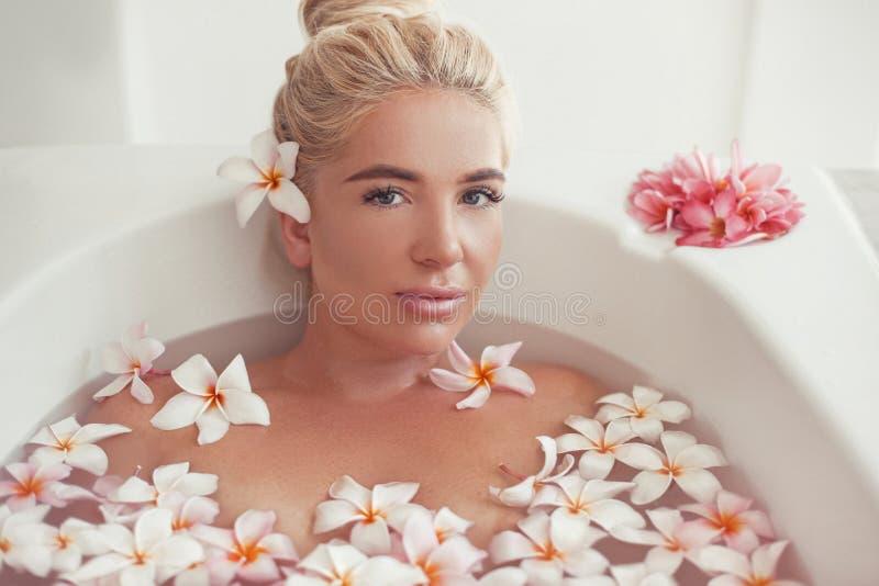 La stazione termale si distende Bagno godente biondo con i fiori tropicali di plumeria Salute e bellezza Bella ragazza sexy del p fotografia stock libera da diritti