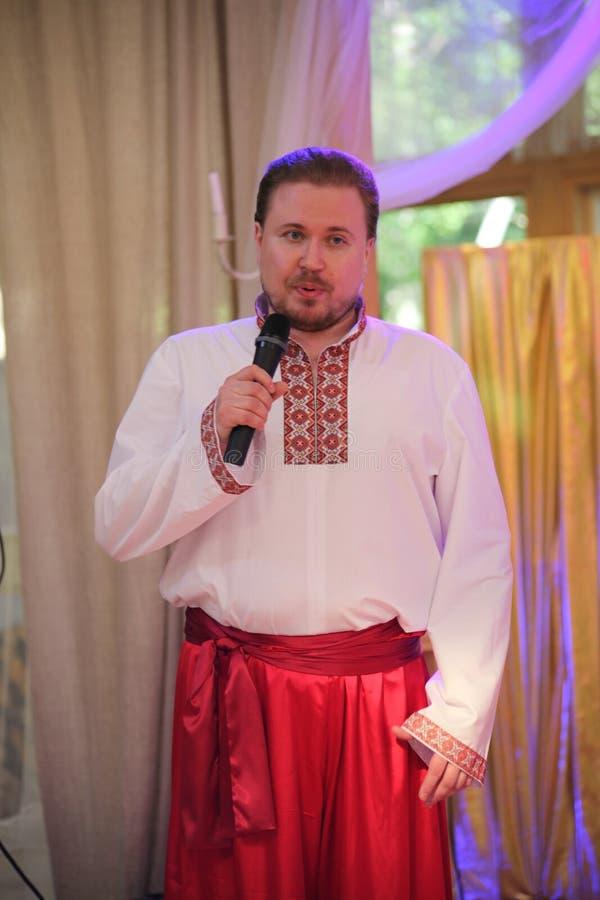 La stella dello spettacolo, cantante di opera, atti di Sergey Muravyov di tenore, canta il costume russo ucraino nazionale fotografia stock libera da diritti