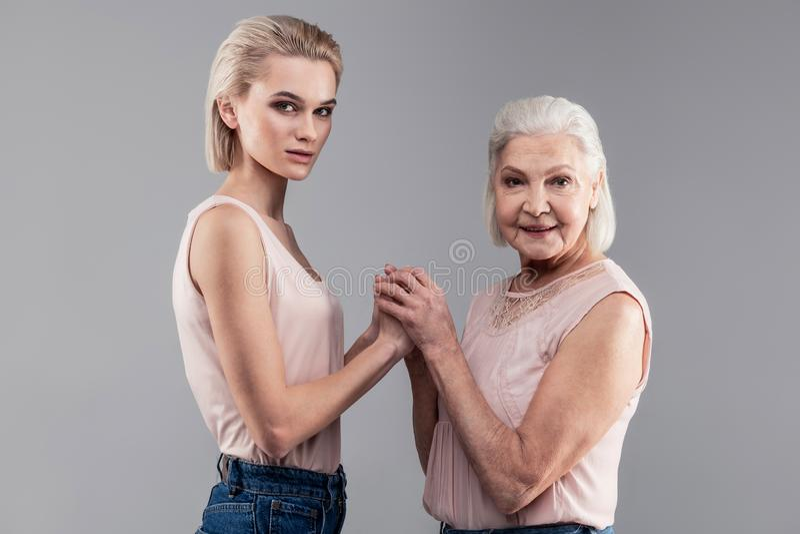 La stessa donna dai capelli corti con gli occhi grigi ma le età differenti immagini stock