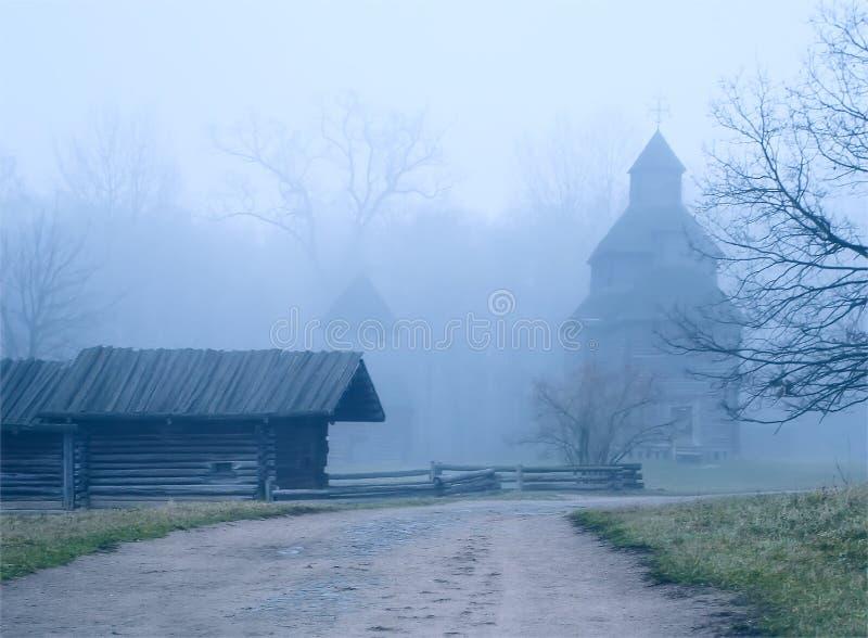 La strada alla chiesa ed alla vecchia casa nella nebbia fotografia stock libera da diritti