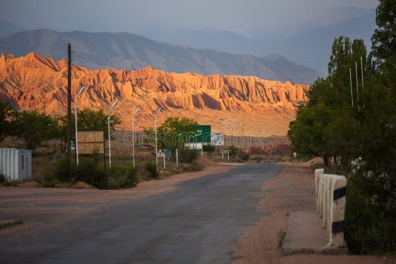 La strada alle rocce, accese brillantemente all'alba Repubblica del Kyrgystan immagine stock libera da diritti