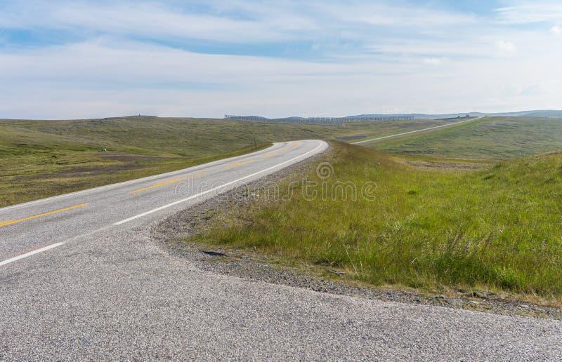 La strada allunga nella distanza su un fondo dei prati verdi fotografia stock libera da diritti