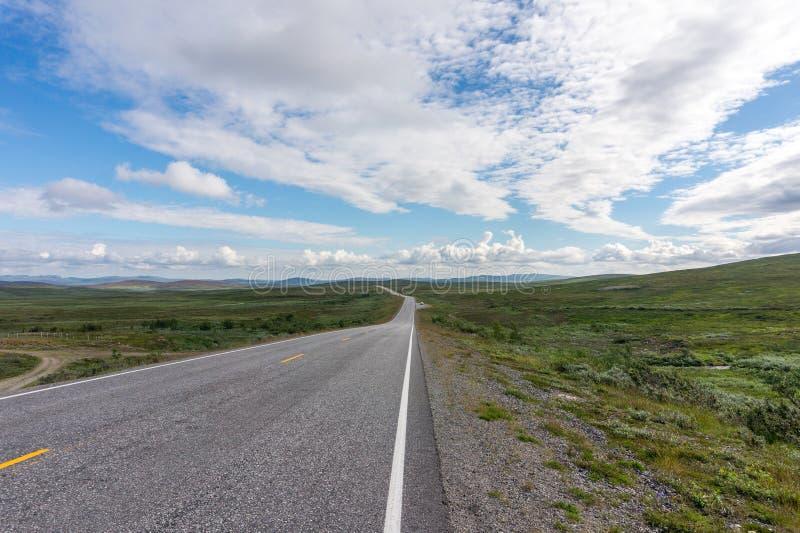 La strada allunga nella distanza su un fondo dei prati verdi immagine stock