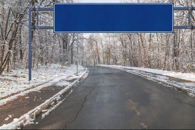 La strada asfaltata con il grande segno verde sull'orlo della città con gli alberi del parco coperti di neve immagini stock
