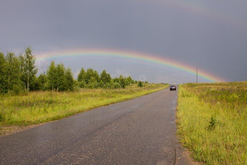 La strada che va all'orizzonte e ad un grande arcobaleno nel cielo fotografia stock