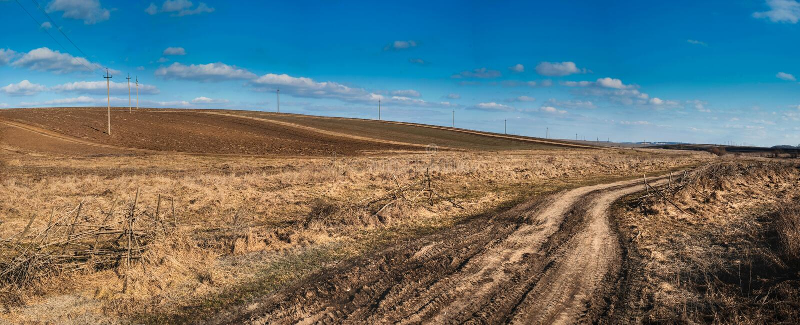 La strada con erba asciutta sui precedenti delle colline un giorno soleggiato in primavera fotografia stock