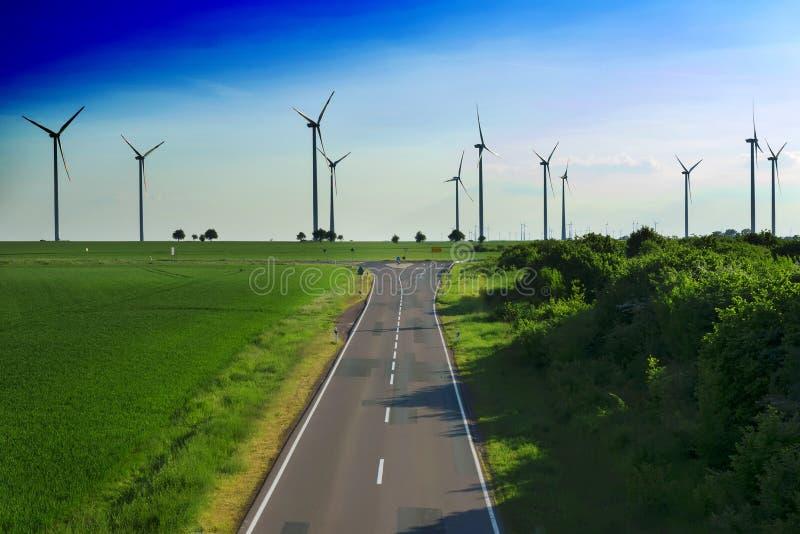 la strada conduce ai generatori eolici producendo l'energia alternativa fotografia stock libera da diritti