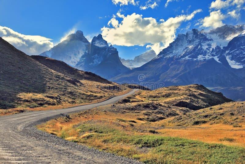 La strada della ghiaia va alle montagne innevate immagine stock libera da diritti