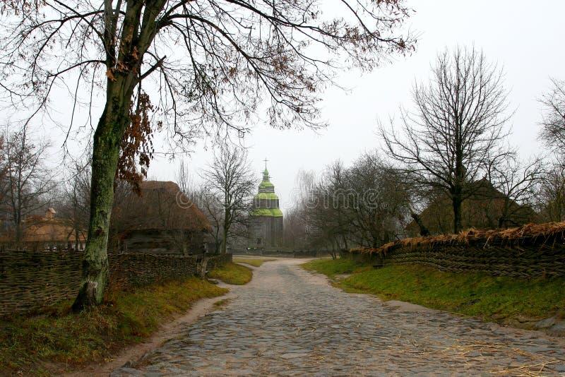 La strada di pietra rurale sta conducendo alla chiesa nel villaggio fotografie stock libere da diritti