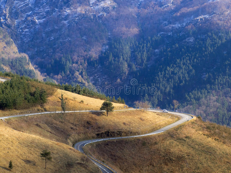 La strada gira intorno una montagna nel parco naturale del Paese Basco fotografie stock libere da diritti