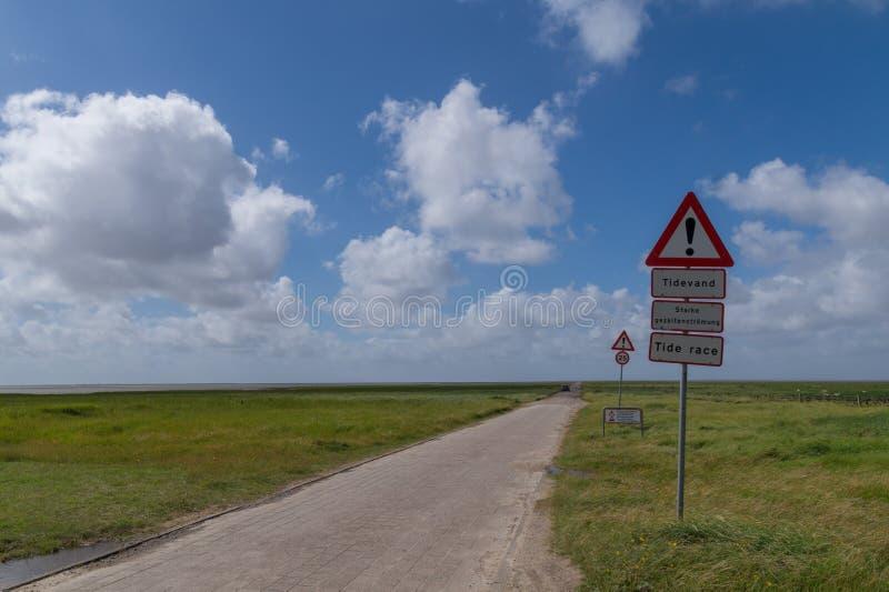 La strada a Mandø, Danimarca con il segnale di pericolo di acqua di marea fotografia stock libera da diritti