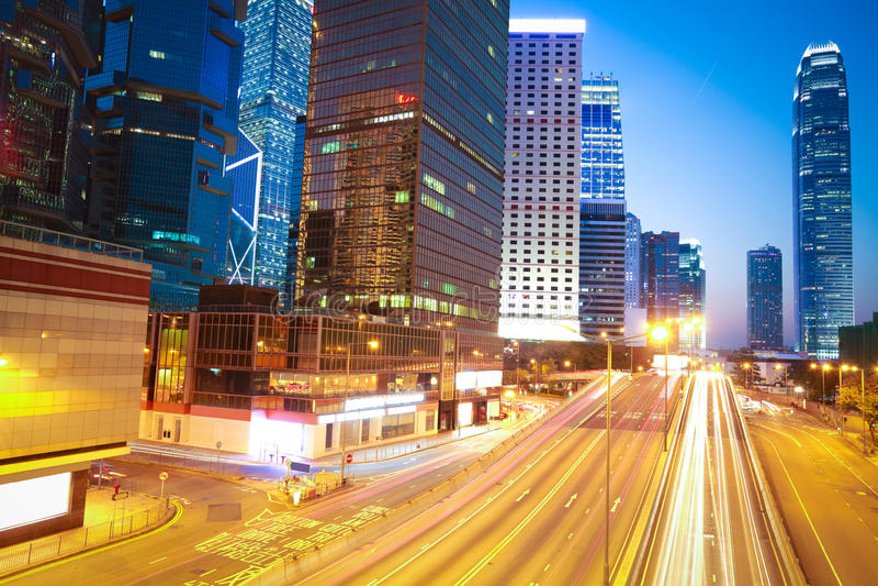 La strada principale trascina la luce sul fondo moderno della costruzione del punto di riferimento fotografia stock libera da diritti