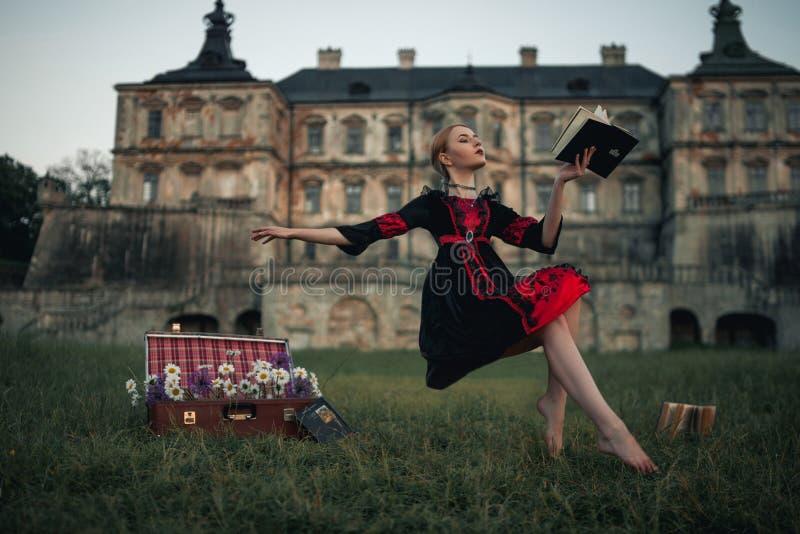 La strega della donna vola in aria e legge il libro contro il contesto del castello antico fotografia stock