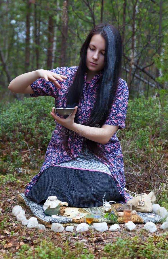 La strega della ragazza evoca nel legno immagine stock libera da diritti