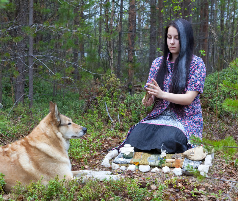 La strega della ragazza evoca nel legno Vicino ad un cane enorme fotografia stock libera da diritti