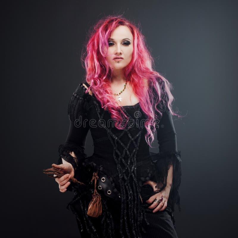 La strega di Halloween crea la magia Donna attraente con capelli rossi in costume delle streghe di voodoo fotografia stock libera da diritti