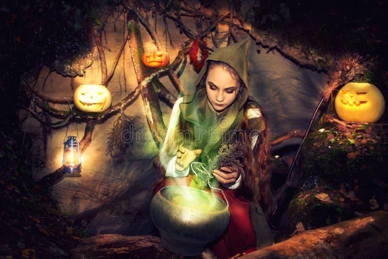 La strega fa le pozioni lei caverna fotografia stock