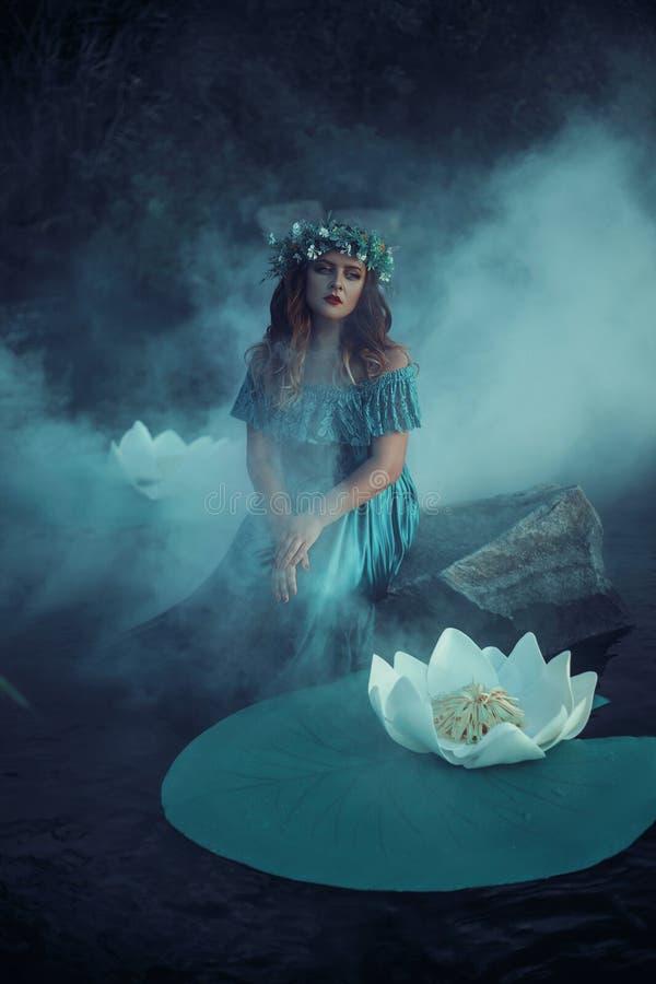 La strega lancia un incantesimo sull'acqua nella nebbia fotografie stock