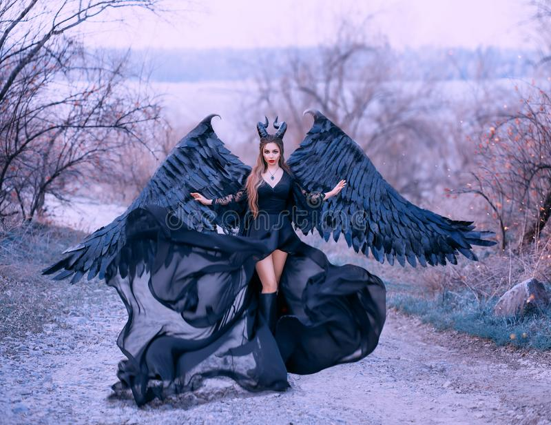 La strega scura splendida incantante controlla il vento, le onde del flusso d'aria orlano e treno lungo del vestito nero leggero  fotografia stock libera da diritti