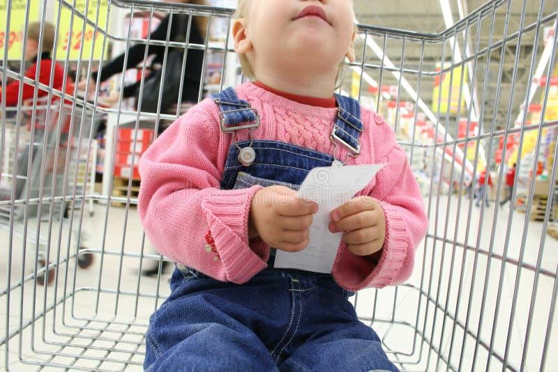 La stretta del bambino controlla lo shopingcart fotografie stock libere da diritti