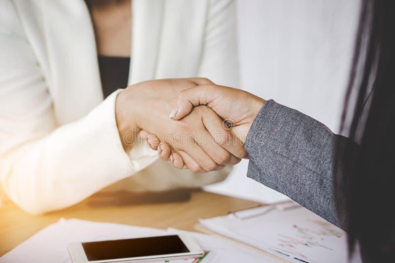 La stretta di mano della donna di affari dei partner acconsente per firmare un contratto fotografie stock libere da diritti