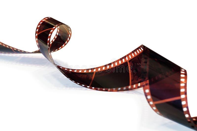 La striscia di pellicola ha arricciato in una spirale su bianco fotografie stock