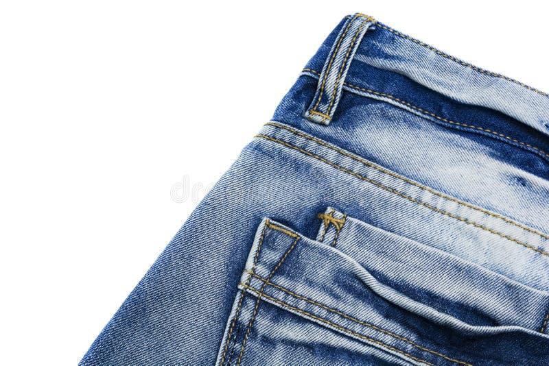 La struttura dei jeans sfilacciati blu con una tasca sull'isolato Fondo del denim fotografie stock libere da diritti