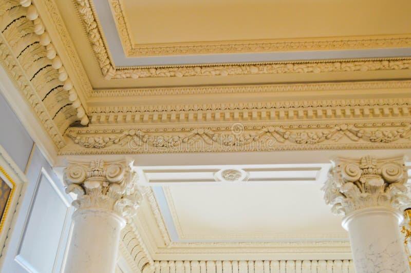 La struttura del soffitto di pietra bianco con i modelli e le belle colonne antiche del modanatura del gesso e I cenni storici fotografia stock libera da diritti