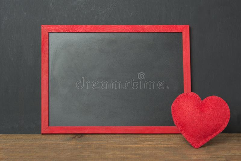 La struttura della lavagna con il posto per il vostri testo e rosso ha ritenuto il cuore come decorazione sulla tavola di legno S immagini stock