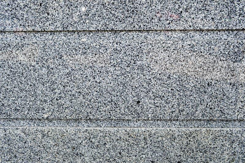 La struttura della parete di pietra è solida liscia delle briciole del granito del nero di due colori e delle bande orizzontali d fotografie stock libere da diritti