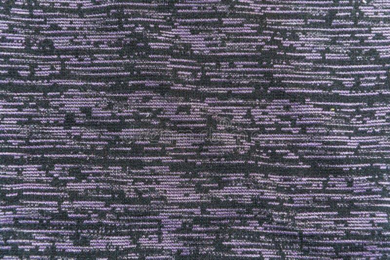 La struttura di tessuto nero con i tocchi orizzontali viola immagini stock