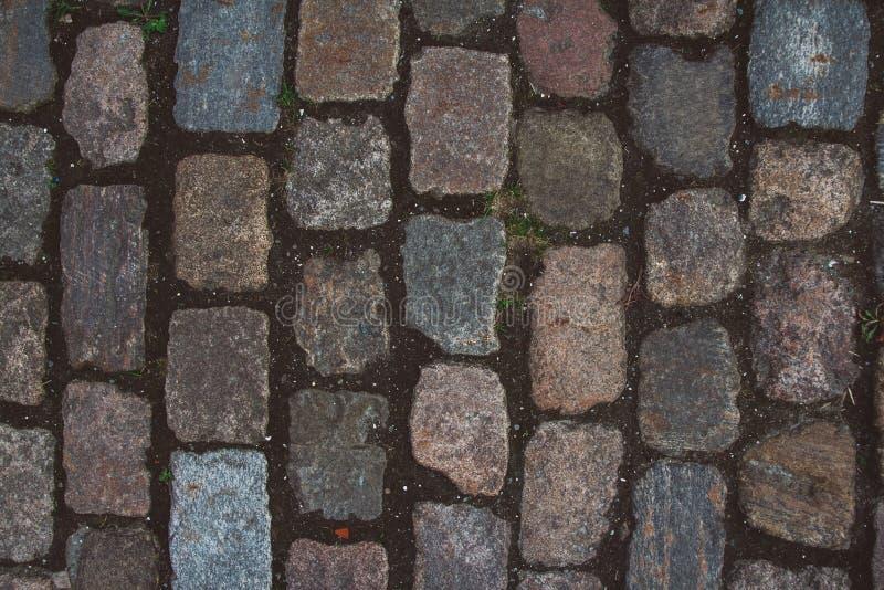 La struttura di vecchio ciottolo e delle pietre insolite Modellato pavimentando la strada del ciottolo delle mattonelle per strut immagini stock