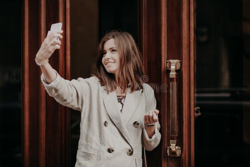 La studentessa adorabile posa per la fabbricazione del selfie, utilizza il telefono cellulare moderno, vestito in rivestimento bi immagini stock libere da diritti