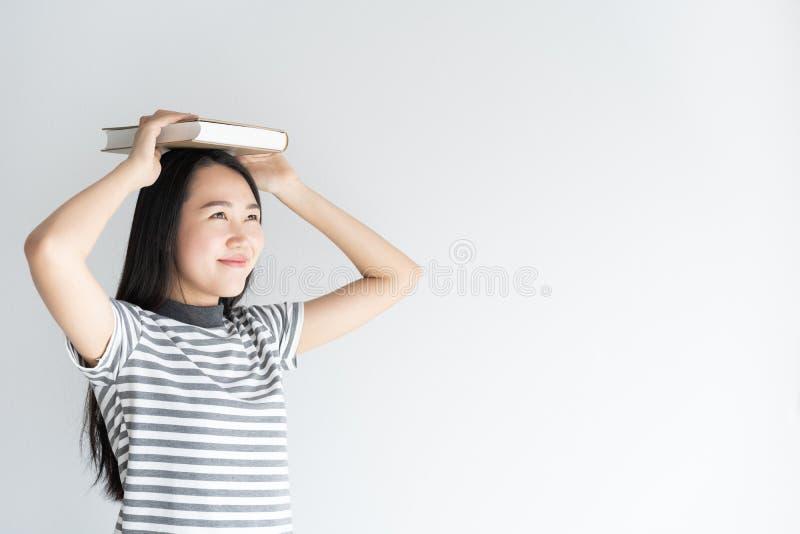 La studentessa asiatica della condizione dell'università sul fondo bianco che tiene un libro sulle donne si dirige Sorridere dell immagini stock