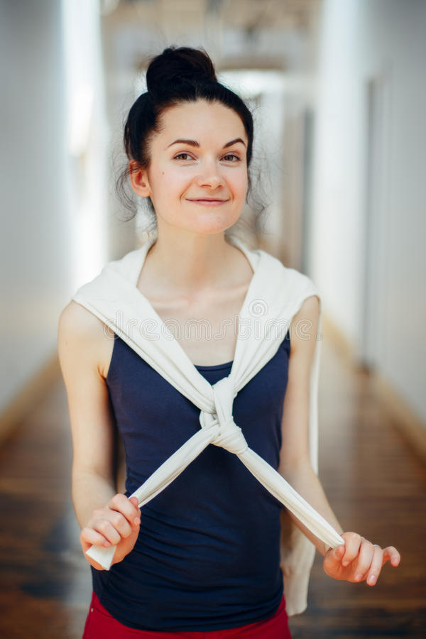 la studentessa bella giovane castana caucasica bianca di risata sorridente con capelli scuri e marrone osserva, stando nel corrid fotografia stock