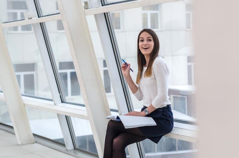 La studentessa con il taccuino e la penna in mani sorprese sorridono fotografia stock
