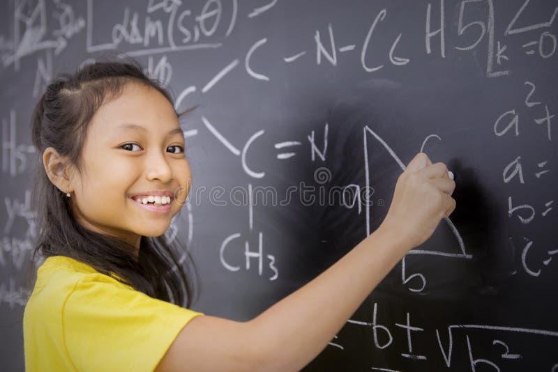 La studentessa felice scrive la formula matematica immagini stock libere da diritti