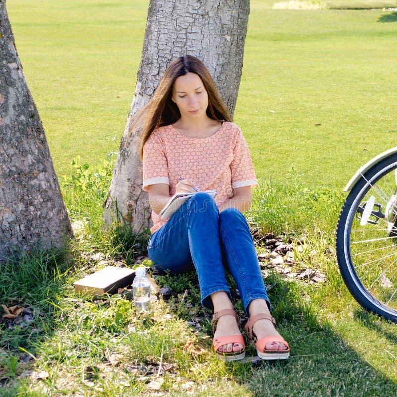 La studentessa felice scrive in taccuino che si siede sotto l'albero immagine stock