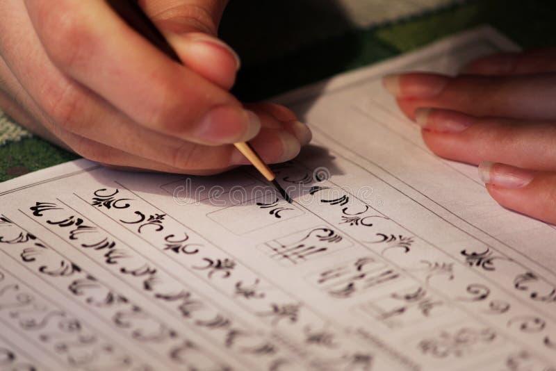 La studentessa impara disegnare i monogrammi per il disegno loro sulle unghie quando crea un manicure con la gomma lacca della la immagini stock libere da diritti