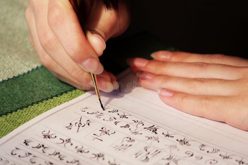 La studentessa impara disegnare i monogrammi per il disegno loro sulle unghie quando crea un manicure con la gomma lacca della la fotografie stock libere da diritti