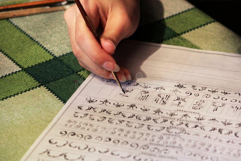 La studentessa impara disegnare i monogrammi per il disegno loro sulle unghie quando crea un manicure con la gomma lacca della la immagine stock