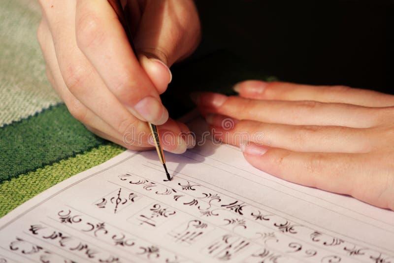 La studentessa impara disegnare i monogrammi per il disegno loro sulle unghie quando crea un manicure con la gomma lacca della la fotografia stock libera da diritti